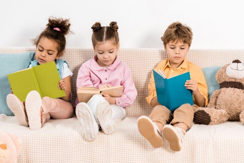3 søde børn der læser bøger i en børnesofa